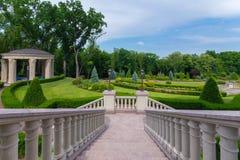 Vaya abajo al callejón del parque con los arbustos y el gazebo verdes con cresta Foto de archivo libre de regalías