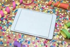 Vaya de fiesta con confeti y la flámula con el espacio libre en ipad Imagen de archivo libre de regalías