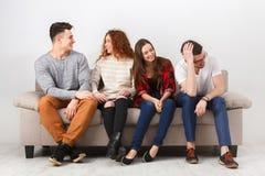Vaya de fiesta con los amigos, gente joven que se sienta en el sofá Imagenes de archivo