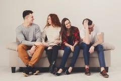Vaya de fiesta con los amigos, gente joven que se sienta en el sofá Imagen de archivo