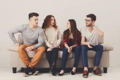 Vaya de fiesta con los amigos, gente joven que se sienta en el sofá Fotografía de archivo libre de regalías