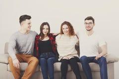 Vaya de fiesta con los amigos, gente joven que se sienta en el sofá Foto de archivo