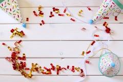 Vaya de fiesta el sombrero al lado de confeti colorido en la tabla de madera Imágenes de archivo libres de regalías