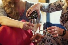 Vaya de fiesta en la limusina - muchachas felices que celebran, mujer vierta el champán - ascendente cercano imágenes de archivo libres de regalías