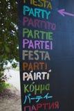 Vaya de fiesta la muestra escrita en diversas idiomas y diversos colores Imágenes de archivo libres de regalías