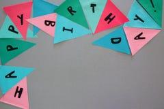 Vaya de fiesta las banderas coloridas en la tabla gris con FELIZ CUMPLEAÑOS de los mundos Fotografía de archivo