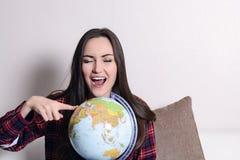 Vaya en una aventura Mujer de la diversión que sueña sobre viajar en todo el mundo, el giro de un globo y señalar al azar el país foto de archivo libre de regalías