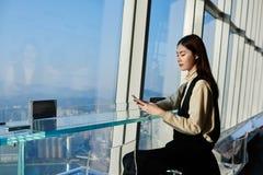 vd:n för ung kvinna kontrollerar bankkonto via mobiltelefonen arkivbilder