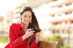 Vídeos de observación de la mujer en un teléfono elegante con los auriculares Imagenes de archivo
