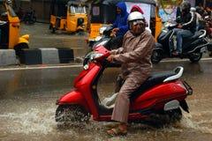 Veículo com rodas indiano da movimentação dois do homem superior em uma estrada inundada imagens de stock royalty free