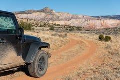 Veículo do quatro rodas motrizes em uma estrada de terra de encurvamento que conduz para um pico alto colorido do deserto no ranc foto de stock