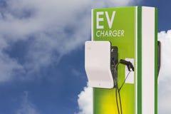Veículo elétrico que carrega a estação de Ev e a tomada da fonte do cabo distribuidor de corrente para o carro de Ev no fundo do  imagem de stock