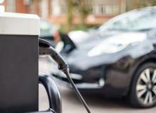 Veículo elétrico que carrega na rua, no Reino Unido imagem de stock