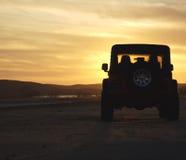 Veículo na região selvagem no por do sol Imagens de Stock