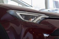 Veículo novo da cor da cereja com as lâmpadas principais elegantes na sala de exposições Imagens de Stock Royalty Free