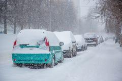 Veículos cobertos com a neve em um blizzard do inverno no parque de estacionamento imagem de stock royalty free