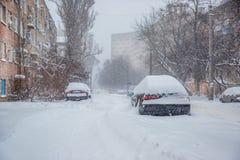 Veículos cobertos com a neve em um blizzard do inverno no parque de estacionamento imagens de stock royalty free