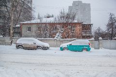 Veículos cobertos com a neve em um blizzard do inverno no parque de estacionamento imagem de stock