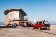 Veículos de socorro da emergência estacionados em Marine Safety Center na praia do luar imagem de stock