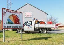 Veículos do departamento dos bombeiros e sinal das avaliações do perigo do fogo Imagens de Stock Royalty Free