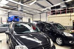 Veículos em uma oficina de reparações do carro para o reparo com platfo de levantamento fotografia de stock royalty free