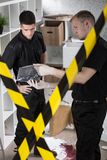 We've got the murder weapon. Two policemen standing behind yellow crime scene tape Royalty Free Stock Photo