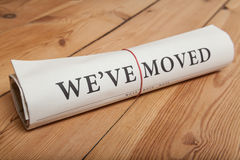 We've moved newspaper. On wooden floor Stock Images