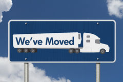 We`ve Moved Sign. A blue Road Sign with text We`ve Moved and a truck with sky background Royalty Free Stock Photos