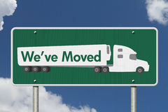 We`ve Moved Sign. A green Road Sign with text We`ve Moved and a truck with sky background Stock Photo