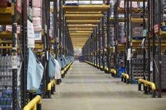 Vea abajo de un pasillo central en un almacén de distribución grande Imágenes de archivo libres de regalías