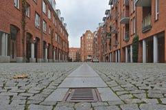 Vea abajo de una calle del guijarro con las casas colgantes con las paredes de ladrillo rojas en ambos lados Imagenes de archivo