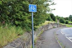 Vea abajo del camino con la pared de piedra vieja y la muestra de ciclo Fotografía de archivo