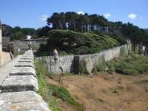 Vea de una colina la pared vieja del castillo en la ciudad de la costa de Baiona Imagen de archivo