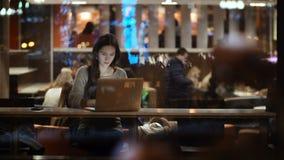Vea dentro de la ventana en la mujer hermosa que se sienta en café y que usa el ordenador portátil La hembra morena hojea Interne almacen de video