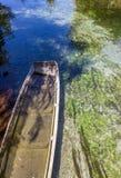 Vea el barco antiguo en un río con reflexiones del árbol Imagen de archivo libre de regalías