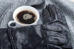 Vea el primer en guantes del ` s de las mujeres negras y una taza del café con leche foto de archivo
