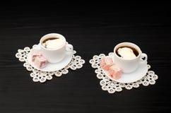 Vea en ángulo en dos tazas de café con el helado, placer turco en un platillo, en las servilletas blancas del cordón Imagenes de archivo