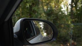 Vea hacia fuera el espejo retrovisor, cuando el coche pasa a lo largo del camino en el verano 4k, tiroteo a c?mara lenta almacen de video