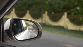 Vea hacia fuera el espejo retrovisor, cuando el coche pasa a lo largo del camino en el verano 4k, tiroteo a c?mara lenta almacen de metraje de vídeo