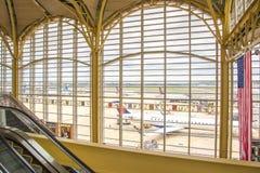 Vea hacia fuera la ventana del aeropuerto a los aeroplanos y a las operaciones de la rampa Fotografía de archivo libre de regalías