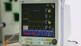 Vea la supervisión de la condición paciente del ` s, muestras vitales en monitor de ICU en hospital almacen de metraje de vídeo