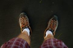 Vea las primeras piernas del hombre de la perspectiva de la persona en la arena volcánica negra Foto de archivo
