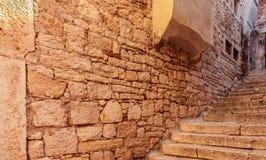 Vea para arriba en las escaleras en calle estrecha y pared de piedra gruesa Foto de archivo