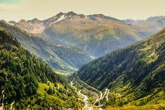 Vea a través del valle de las montañas cerca de Gletch con el ro de la montaña del paso de Furka Fotografía de archivo