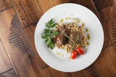 Veal beef cheeks with pearl barley. Porridge and greens in a white plate. Wooden background Stock Image