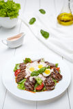 Veal beef fillet medallions warm salad with tomatoes, cucumber, sauce Royalty Free Stock Photography