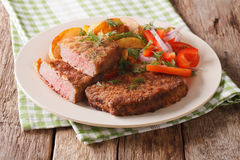 Veal breaded rump steak and garnished with vegetables close-up. Veal breaded rump steak and garnished with vegetables close-up on a plate. horizontal Stock Photo