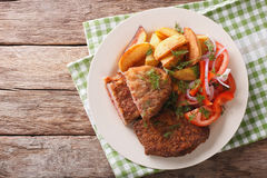Veal breaded rump steak and garnished with vegetables close-up. Stock Photo