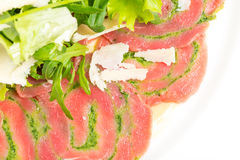 Veal carpaccio with fresh herbs and parmesan. Royalty Free Stock Image