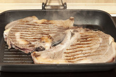 Veal chops being cooked on a grill Royalty Free Stock Photography